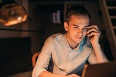 Усмехаясь молодой бизнесмен крепко на работе поздно вечером Стоковые Изображения RF