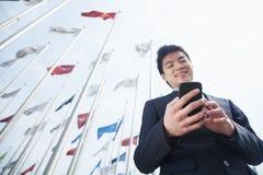 Усмехаясь молодой бизнесмен отправляя СМС на его телефоне outdoors с флагами на заднем плане стоковые фотографии rf