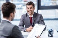 Усмехаясь молодой бизнесмен смотря менеджера с доской сзажимом для бумаги на собеседовании для приема на работу Стоковое Изображение