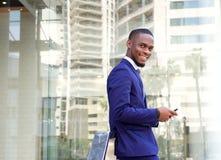 Усмехаясь молодой бизнесмен с мобильным телефоном Стоковое фото RF