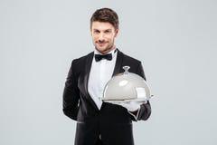 Усмехаясь молодой дворецкий держа поднос с серебряным куполом ресторанного обслуживании стоковое фото