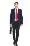 Усмехаясь молодой идти бизнесмена стоковое фото rf