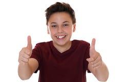 Усмехаясь молодой мальчик подростка показывая большие пальцы руки вверх Стоковые Фотографии RF
