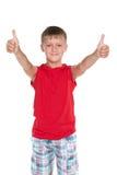 Усмехаясь молодой мальчик с его большими пальцами руки вверх Стоковые Фотографии RF