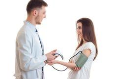 Усмехаясь молодой доктор принимает давление девушки Стоковое Изображение