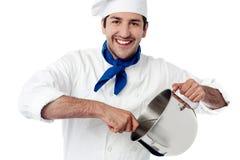 Усмехаясь молодой сосуд удерживания шеф-повара стоковое изображение rf