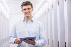 Усмехаясь молодой техник работая с его таблеткой Стоковая Фотография RF