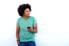 Усмехаясь молодой чернокожий человек держа мобильный телефон стоковые изображения rf
