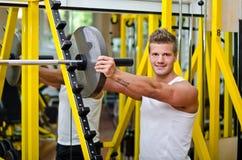 Усмехаясь молодой человек в спортзале кладя диск веса на штангу Стоковые Изображения