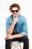 Усмехаясь молодой человек в шляпе и солнечных очках сидя на стуле Стоковое фото RF
