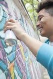 Усмехаясь молодой человек держа картину баллончика и брызга на стене снаружи Стоковые Фотографии RF