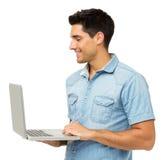Усмехаясь молодой человек используя компьтер-книжку стоковая фотография