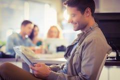 Усмехаясь молодой человек используя цифровую таблетку стоковая фотография