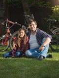 Усмехаясь молодой человек и милая девушка ослабляя на траве на парке позже Стоковое Фото
