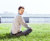 Усмехаясь молодой человек ослабляет на зеленой лужайке Стоковые Фотографии RF