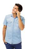 Усмехаясь молодой человек отвечая умному телефону стоковые фотографии rf