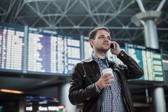Усмехаясь молодой человек путешественника на авиапорте говоря на телефоне перед доской расписания Стоковая Фотография