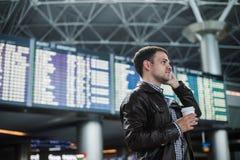 Усмехаясь молодой человек путешественника на авиапорте говоря на телефоне перед доской расписания Стоковое фото RF