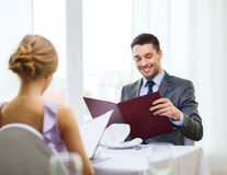 Усмехаясь молодой человек смотря меню на ресторане Стоковые Фотографии RF