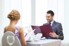 Усмехаясь молодой человек смотря меню на ресторане Стоковые Изображения RF