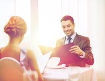 Усмехаясь молодой человек смотря меню на ресторане Стоковая Фотография RF