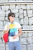 Усмехаясь молодой человек смотря отсутствующий пока стоящ против каменной стены Стоковое Изображение RF