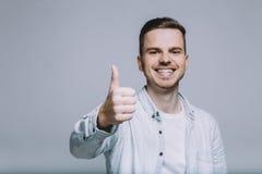 Усмехаясь молодой человек с бородой в белой рубашке с большим пальцем руки вверх стоковое фото rf