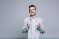 Усмехаясь молодой человек с бородой в белой рубашке стоковые фотографии rf
