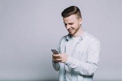 Усмехаясь молодой человек с бородой в белой рубашке стоковое фото