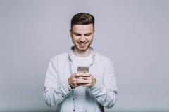 Усмехаясь молодой человек с бородой в белой рубашке стоковая фотография rf