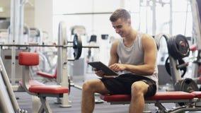 Усмехаясь молодой человек с компьютером ПК таблетки в спортзале видеоматериал
