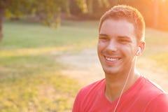 Усмехаясь молодой человек слушая к музыке стоковые фото