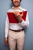Усмехаясь молодой человек читая Красную книгу стоковые фото