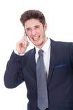 Усмехаясь молодой экзекьютив используя мобильный телефон Стоковые Изображения