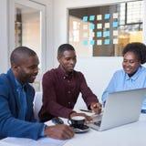 Усмехаясь молодые африканские сотрудники используя компьтер-книжку в офисе Стоковая Фотография