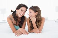 Усмехаясь молодые женские друзья лежа в кровати Стоковые Фотографии RF