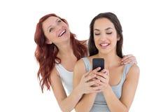 Усмехаясь молодые женские друзья с мобильным телефоном Стоковые Фотографии RF