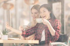 Усмехаясь молодые женщины выпивая кофе и используя цифровую таблетку совместно Стоковое Фото