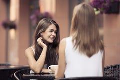 Усмехаясь молодые женщины выпивая кофе Стоковые Изображения RF