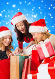 Усмехаясь молодые женщины в шляпах santa с подарками Стоковые Изображения RF