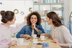 Усмехаясь молодые женщины говоря в кафе Стоковые Фотографии RF