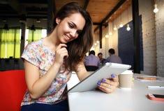 Усмехаясь молодые женщины используя цифровую таблетку в офисе Стоковая Фотография