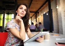 Усмехаясь молодые женщины используя цифровую таблетку в офисе Стоковое Изображение RF
