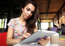 Усмехаясь молодые женщины используя цифровую таблетку в офисе Стоковые Фото