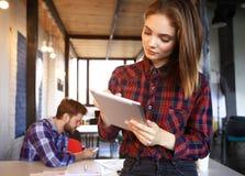 Усмехаясь молодые женщины используя цифровую таблетку в офисе Стоковые Изображения RF
