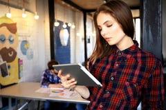 Усмехаясь молодые женщины используя цифровую таблетку в офисе Стоковое Изображение