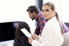 Усмехаясь молодые женщины используя цифровую таблетку в офисе Стоковые Фотографии RF