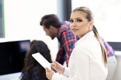 Усмехаясь молодые женщины используя цифровую таблетку в офисе Стоковое фото RF