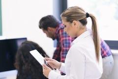 Усмехаясь молодые женщины используя цифровую таблетку в офисе Стоковые Изображения