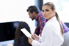 Усмехаясь молодые женщины используя цифровую таблетку в офисе Стоковое Фото